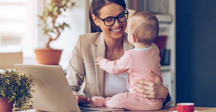Businesswoman holding baby smiling