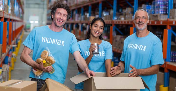 "Three smiling people in blue shirts that say ""Volunteer"" standing in a warehouse putting food in boxes"