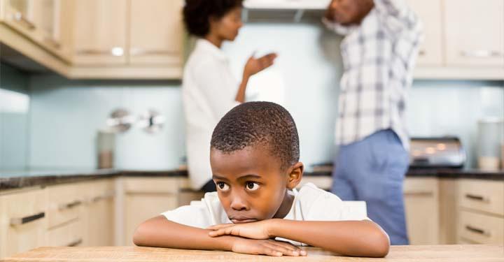 Young boy sadly resting his chin on his crossed arms on a table while his parents argue behind him