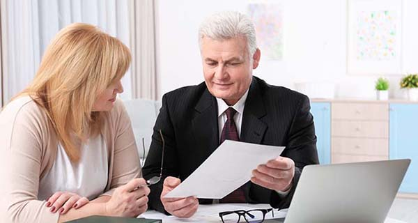 Older man in suit shows older woman in pink sweater document in front of laptop