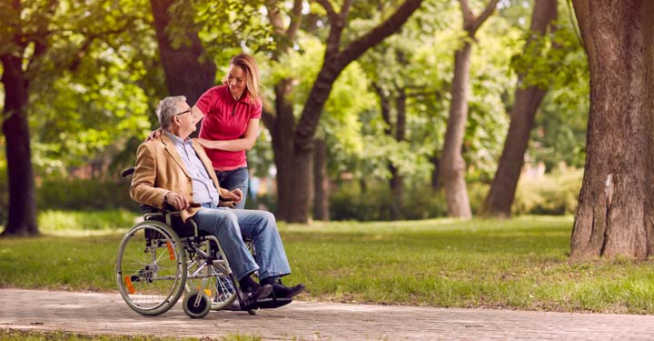 Woman standing over the shoulder of an elderly man in a wheel chair sitting in a park