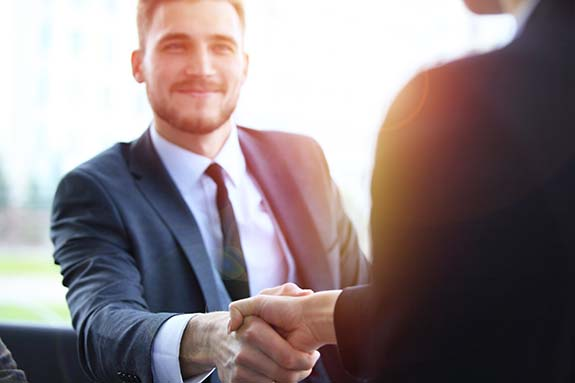 Man in suit shaking other person's hand