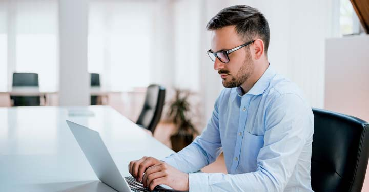 Man in glasses using laptop at office desk
