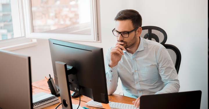 Man wearing glasses sitting at desk using computer