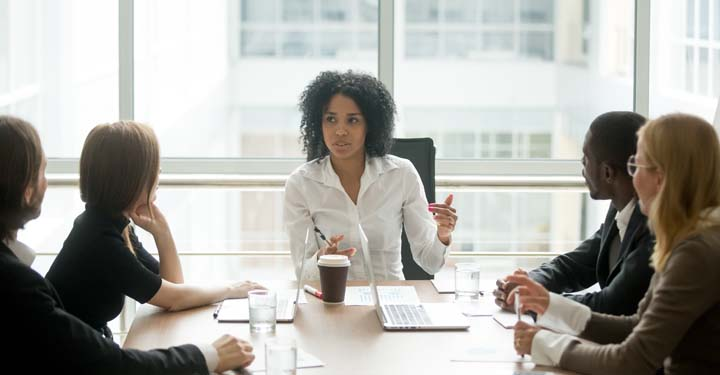 Woman head of conference table with coworkers with full length windows behind her