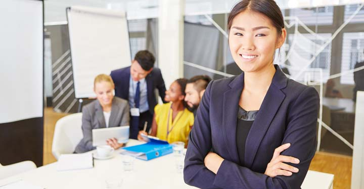 Smiling businesswoman with coworkers working behind her