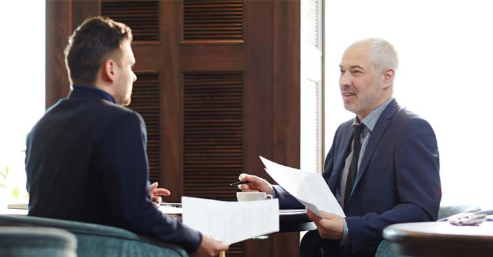Two suited men talking and holding paperwork