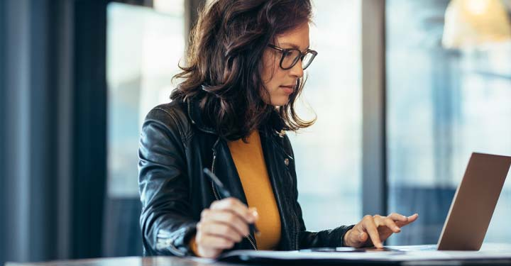 Woman wearing glasses and leather jacket holding a pen in one hand and using her laptop with the other