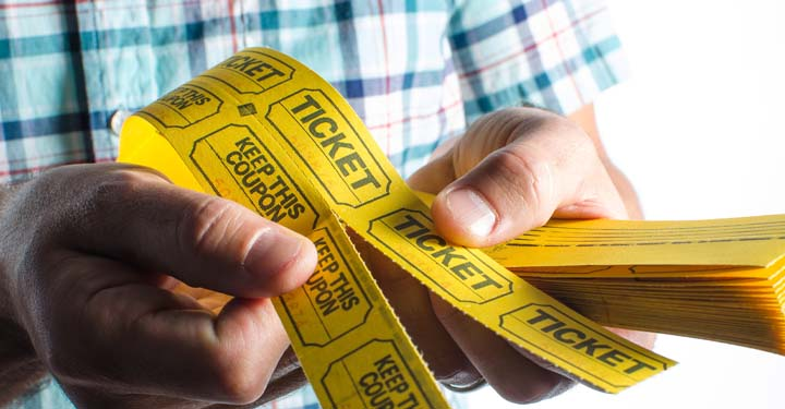 Person holding a roll of yellow tickets
