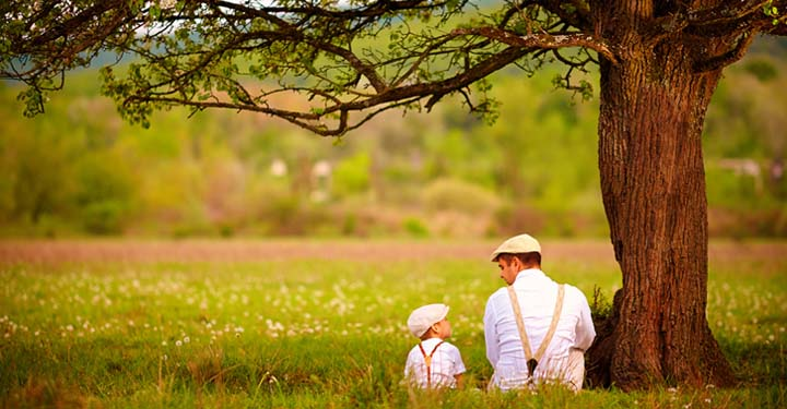 Man and toddler son sitting under tree in field and looking at each other while wearing matching outfits: caps, suspenders, and button up shirts