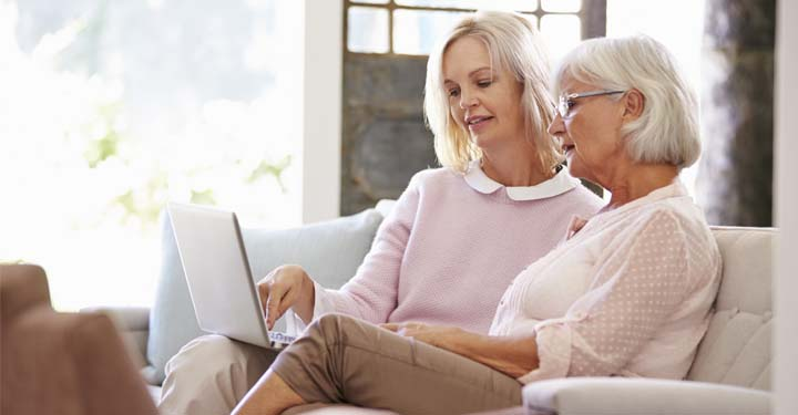 Two older women looking at laptop while sitting on couch