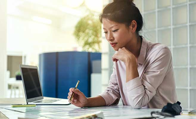 Woman holding pen over paper in office