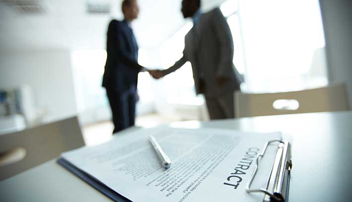 Businesspeople shaking hands in front of contract lying on table