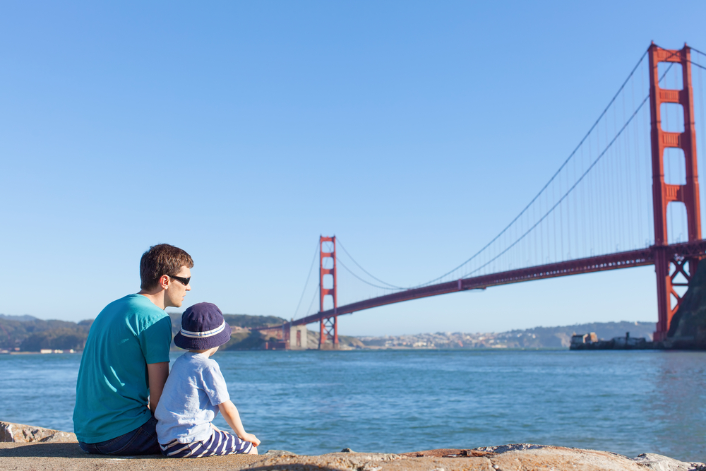 Man and child looking at golden gate bridge together