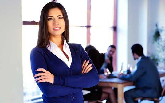 Businesswoman crossing arms in office