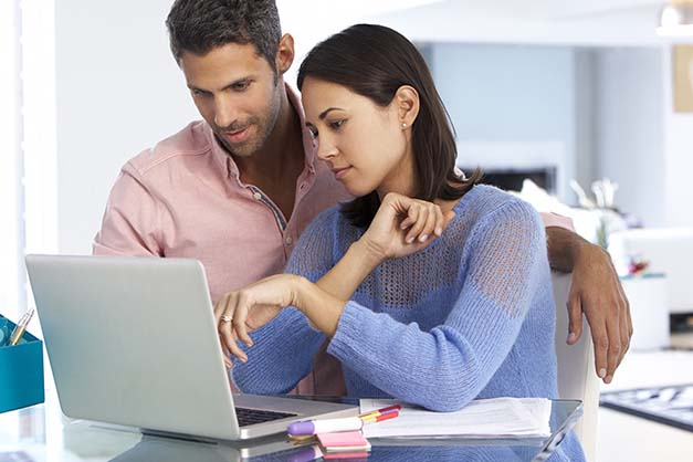 Couple looking at laptop at desk