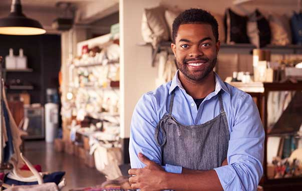 Man in apron stands in workshop
