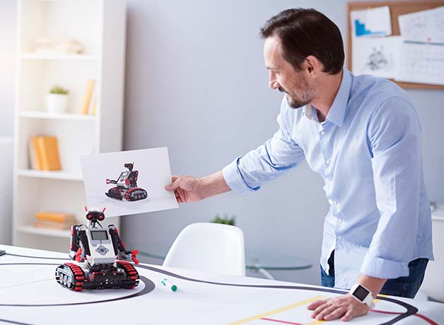 Man at desk holding up design of robot next to actual robot