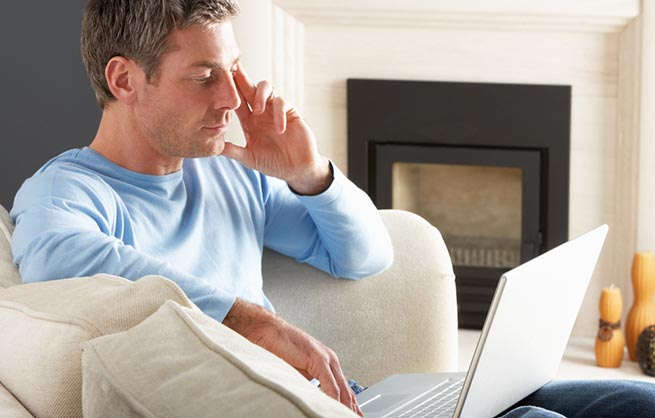 Man in blue sweater looking down at laptop in lap