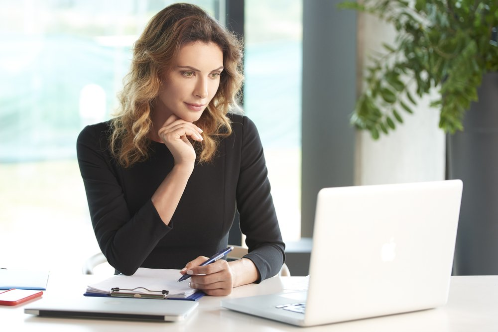 Curly haired woman gazing into laptop screen