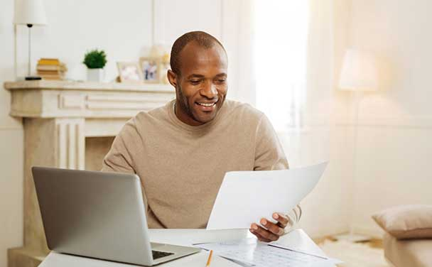 Man smiling while looking at papers in front of white fireplace