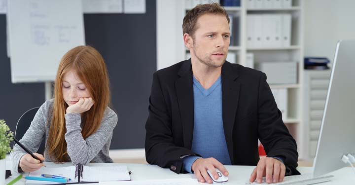 Little girl with straight, red hair writing in a notebook sitting at a desk next to a man working on a computer