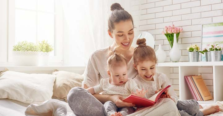 Woman holding two young children reading a book