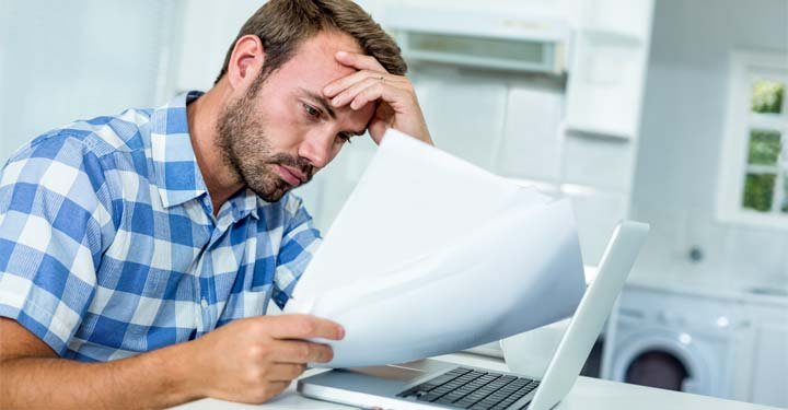Frustrated man reading paperwork
