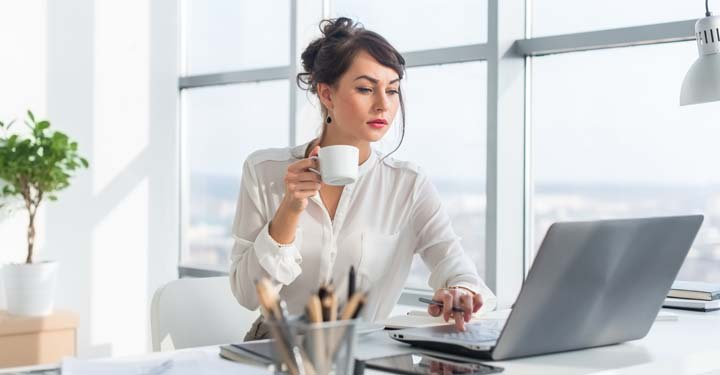 Woman sitting at a table holding a coffee cup and using a laptop