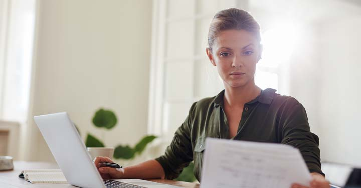 Woman reading paperwork while sitting at laptop