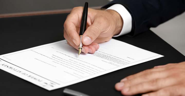 Person signing a document labeled Power of Attorney with a fountain pen