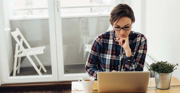 Woman in plaid shirt using laptop
