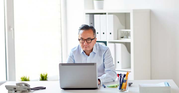 Man wearing glasses sitting at office desk using laptop