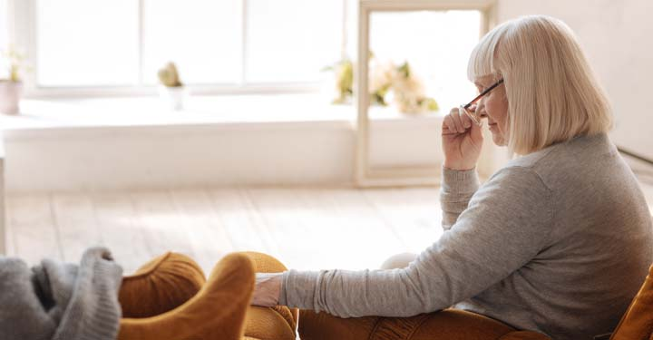 Elderly woman taking off her glasses, sitting in her home