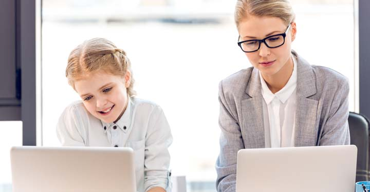 Daughter and mother sitting next to each other at a desk using respective laptops