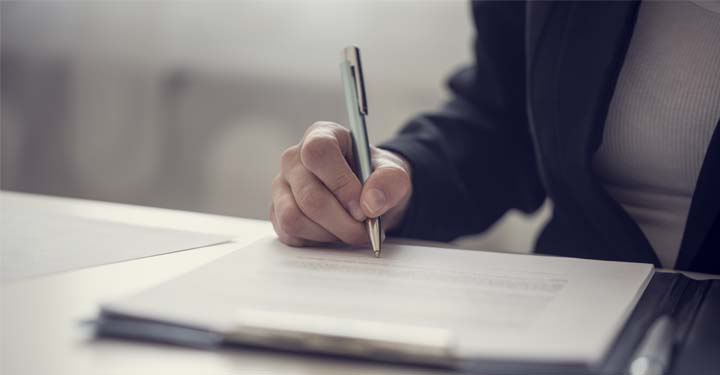 Person using a silver pen to sign documents on a clipboard