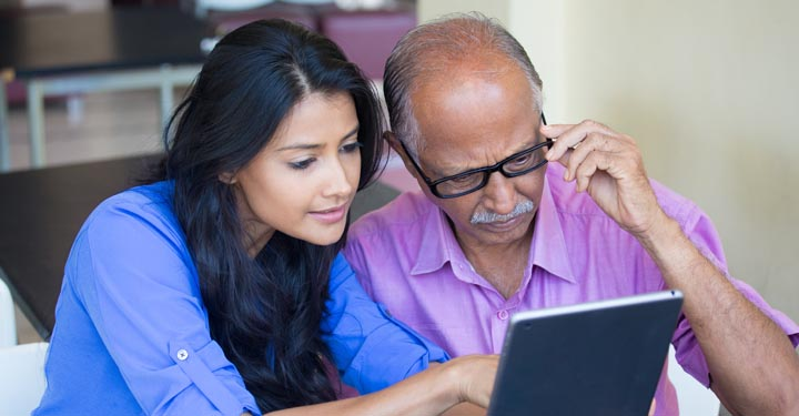 Young woman and elderly man looking at a tablet together