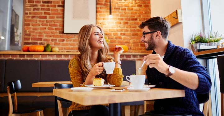 Woman and man sitting in a coffee shop holding white mugs and laughing