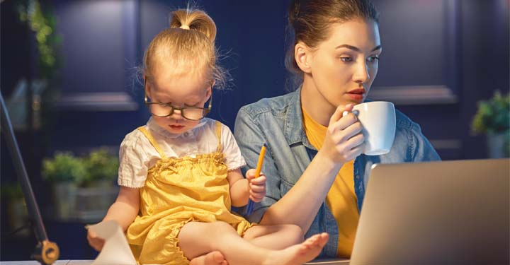 Woman working at a computer while drinking a cup of coffee next to a young girl sitting on the table next to her