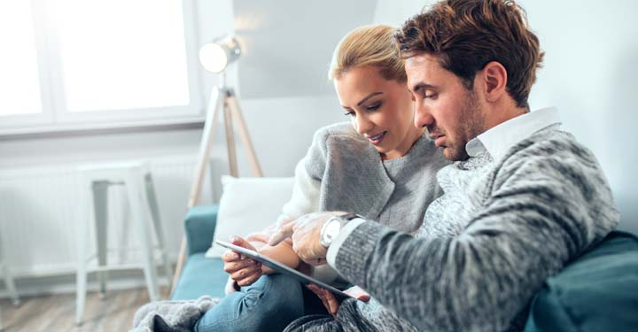Man and woman sitting together on a couch using tablet