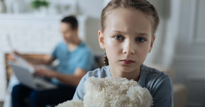 Little girl looking sad and holding a teddy bear