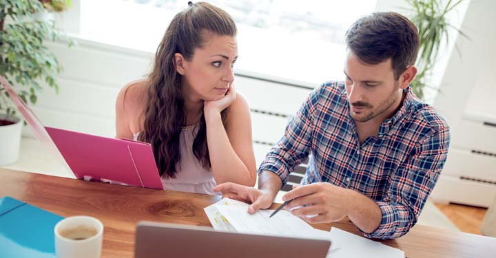 Woman holding a folder and looking at a man as he reviews documents