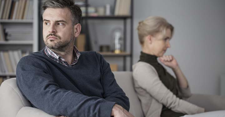 Man and woman uncomfortably sitting on opposite ends of a couch looking away from each other