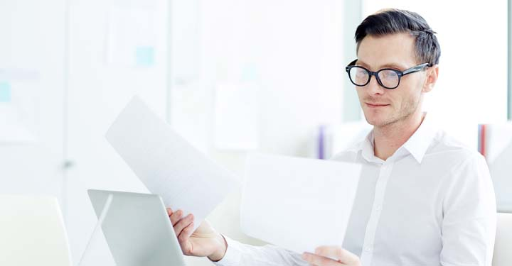 Man wearing glasses and reading paperwork