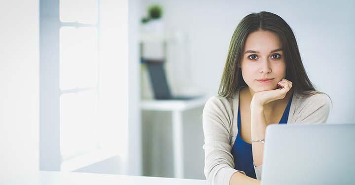 Brunette girl sitting in front of laptop in minimalist office space