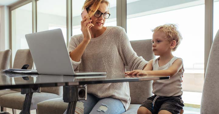 Mother talking on the phone and sitting next to her son at a conference table looking at an open laptop