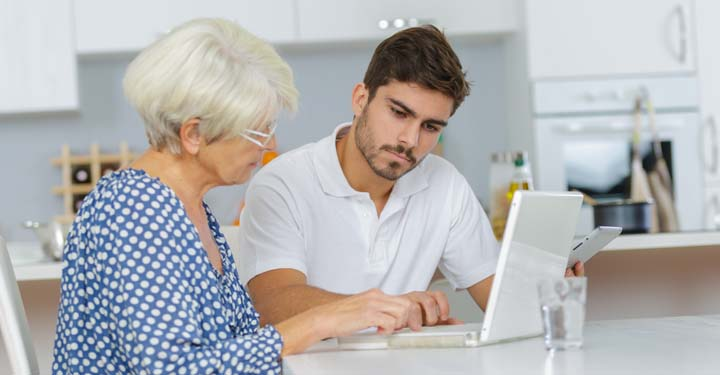 Man and elderly woman working on a laptop together