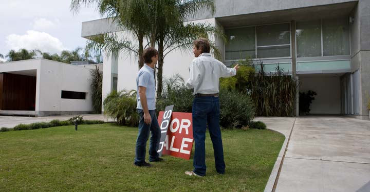 "Man and woman standing outside a home with a ""For Sale"" sign"