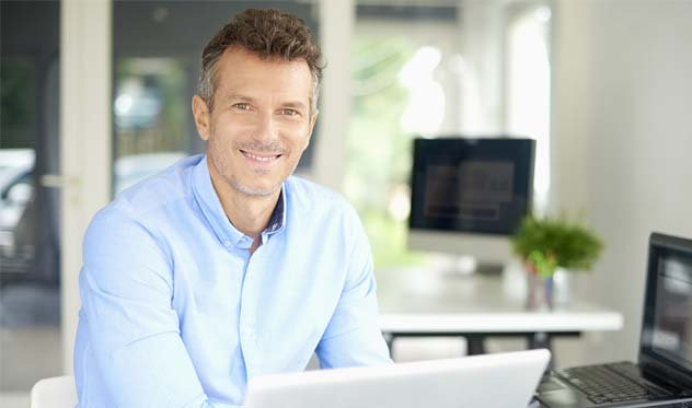 Man in button down shirt smiling while sitting at desk
