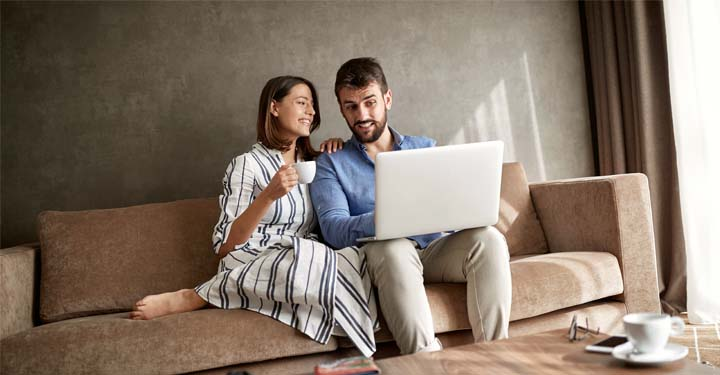 Couple sitting together on a couch using a laptop